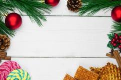奶蛋烘饼用桂香和茴香星和棒棒糖 分支圣诞树和红色球与锥体在白色木葡萄酒backgroun 免版税图库摄影