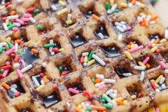 奶蛋烘饼用熔化巧克力和五颜六色的闪闪发光 免版税图库摄影