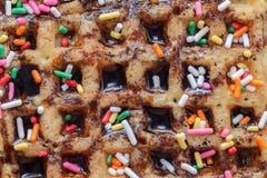 奶蛋烘饼用熔化巧克力和五颜六色的闪闪发光 库存照片