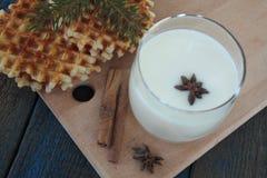 奶蛋烘饼用牛奶,桂香,在蓝色木背景的茴香 免版税库存图片