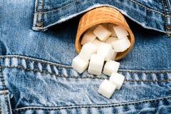 奶蛋烘饼锥体用在牛仔布背景的精制糖 充分锥体在牛仔裤的口袋的精制糖 冰淇凌的锥体 库存照片