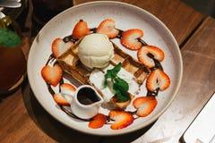 奶蛋烘饼顶部顶视图与香草冰淇淋,鞭子奶油瓢的,切了草莓、薄荷叶和巧克力汁 库存图片