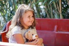 她享受一个可爱的夏日,当拥抱她喜爱的玩具时 库存图片