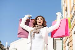 她喜爱购物。低角度视图愉快少妇站立 免版税库存图片