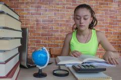 她在一本大书找到入她的笔记本的女孩和文字信息 免版税库存图片