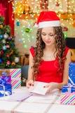 她在信封投入与圣诞节问候的一张明信片 免版税库存照片