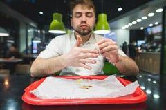 她在午餐以后抹她的手指在快餐餐馆 人在桌和盘子上从调味汁清洗手 库存照片