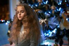 她在圣诞树附近藐视小女孩 免版税图库摄影