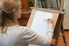 她在艺术家演播室的铅笔画象的一个画架绘 免版税库存图片