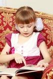 她坐长沙发并且读书 免版税图库摄影