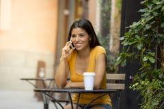 她巧妙的电话的可爱的拉丁妇女 库存照片