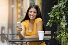 她巧妙的电话的可爱的拉丁妇女 图库摄影