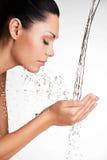 洗她干净的面孔用水的妇女 免版税库存图片