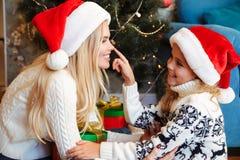 她微笑的圣诞老人` s帽子感人的鼻子的逗人喜爱的矮小的女儿 免版税库存图片