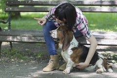 她爱狗 妇女坐一条长凳在有他的好漂亮的东西或人的公园 免版税库存照片