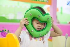 她的与绿色心脏的眼睛把枕在的逗人喜爱的亚洲小女孩关闭 免版税库存照片