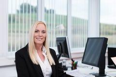 她的书桌的可爱的女实业家 免版税库存图片