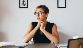 她的书桌的妇女在办公室 免版税图库摄影