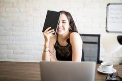 她的书桌的快乐的少妇 库存照片