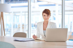 她的书桌的现代年轻女实业家在一个明亮的办公室 图库摄影