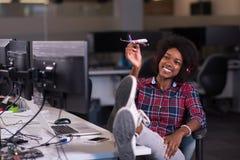 她的使用与平面玩具的办公室工作场所的少妇 免版税库存图片