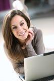 她的使用妇女的膝上型计算机客厅 图库摄影