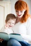 读她的儿子书的妈妈 免版税库存图片