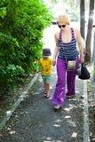 她的儿子走的妇女 免版税库存图片