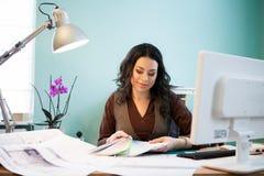 她的办公桌的愉快的建筑师妇女 免版税图库摄影