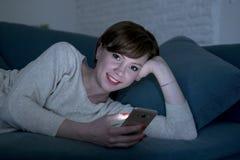她的后说谎在家庭长沙发的20s的年轻俏丽和愉快的红色头发妇女或30s或床使用手机在夜微笑的relaxe 免版税库存图片