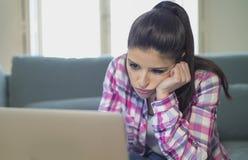 她的在家运作客厅的30s的年轻可爱和乏味拉丁妇女坐有便携式计算机的长沙发在重音神色 图库摄影
