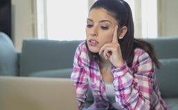 她的在家运作客厅的30s的年轻可爱和乏味拉丁妇女坐有便携式计算机的长沙发在重音神色 免版税库存照片