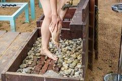 洗她的在沙子海滩的妇女脚 库存图片
