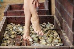 洗她的在沙子海滩的妇女脚 免版税图库摄影