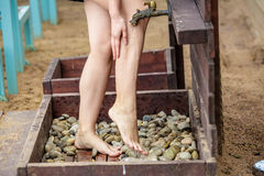 洗她的在沙子海滩的妇女脚 库存照片