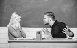 她的坏消息 沮丧的坐在书桌的老师和男校长 帅哥和逗人喜爱的妇女回到学校 免版税图库摄影
