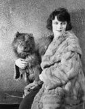 她的坐与她的狗的皮大衣的妇女(所有人被描述不更长生存,并且庄园不存在 供应商保单 免版税库存图片