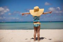 她的太阳帽子的女婴在海滩 免版税库存照片