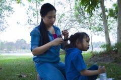 她的太阳的愉快的亚洲母亲领带头发,当吃快餐时的可爱的男性孩子 库存图片