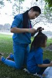 她的太阳的愉快的亚洲母亲领带头发,当吃快餐时的可爱的男性孩子 免版税库存图片