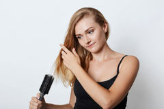 她的头发美好的白肤金发的女性采取的关心的图片,梳它在洗澡以后,被隔绝在白色背景 Gorgeo 免版税库存照片