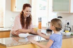 给她的女儿橙汁的母亲 免版税库存照片