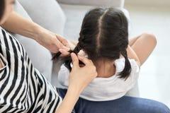 她的女儿的母亲把编成辫子的头发 免版税库存照片