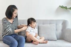 她的女儿的母亲把编成辫子的头发 库存照片