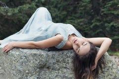 她的婚礼礼服一级风的美丽的甜女孩新娘在湖,山一个美好的风景附近的山  免版税图库摄影