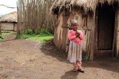她的小屋前面的少女在马塞人村庄 免版税库存照片