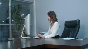 她的工作场所的年轻亚裔女实业家在办公室 免版税库存照片