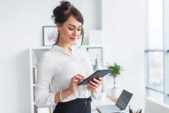 她的工作场所读书的年轻人微笑的女性办公室工作者,浏览新闻使用片剂计算机的广告消息,当时 库存照片