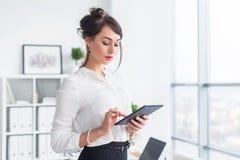 她的工作场所读书的年轻人微笑的女性办公室工作者,浏览新闻使用片剂计算机的广告消息,当时 免版税库存照片