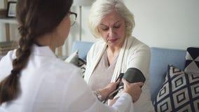 她的房子的医师参观老妇人测量的压力的 影视素材